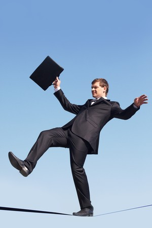 Photo of careful businessman standing on ribbon or rope running risk of falling down photo