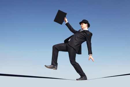 Photo of careful businessman standing on ribbon or rope running risk of falling down Stock Photo - 7873745