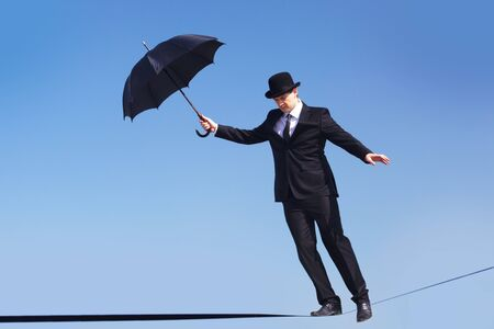 hábil: Photo of skilled businessman with open umbrella walking down ribbon or rope Banco de Imagens