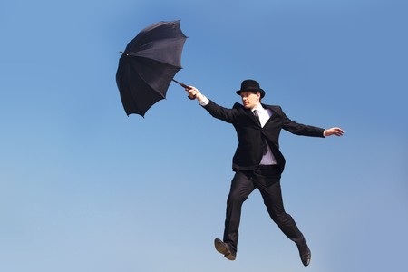 Photo of businessman flying on umbrella with blue sky at background  photo