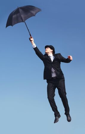 agility people: Photo of businessman flying on umbrella with blue sky at background