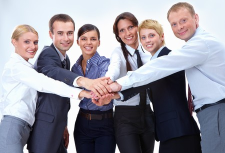 coworker: Portrait of friendly business team keeping their hands on top of each other and looking at camera