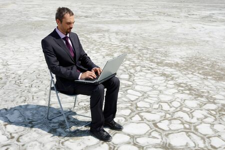 Photo of modern businessman typing on laptop outside photo