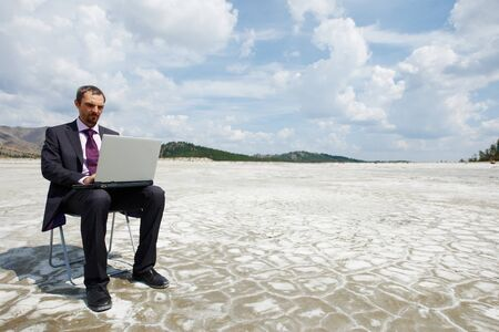 Photo of modern businessman typing on laptop outside with cloudy sky above photo