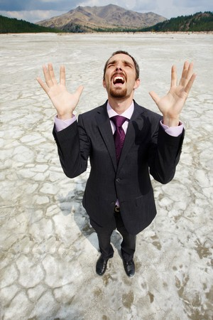 helpless: Photo of helpless businessman standing on dry ground and screaming with raised arms Stock Photo
