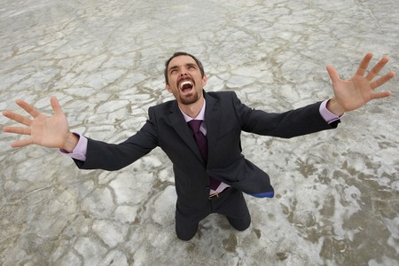 СОС: Photo of crying businessman standing on dry ground and raising his arms upwards