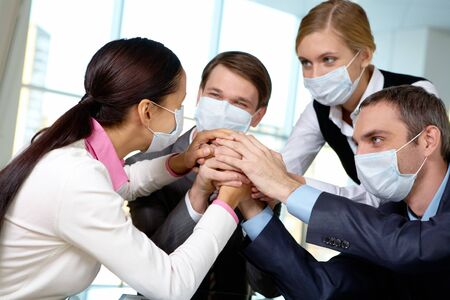 Portrait of business team in protective masks making pile of hands photo