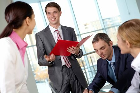 Image of businessman answering questions of colleagues at meeting photo