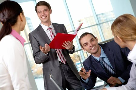Image of several colleagues interacting at meeting in office photo