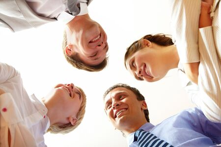 competitive: Below angle of happy business people looking at each other