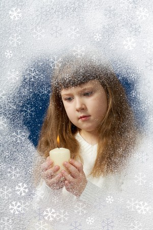 Image of youthful girl with candle in hands looking at it behind window photo