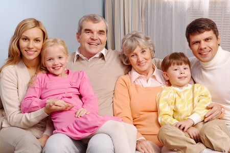 Portrait of senior and young couples with their children sitting on sofa at home Stock Photo - 7873849