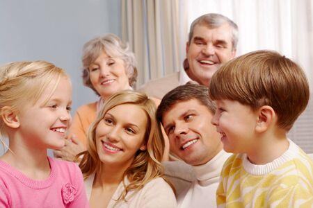Portrait of boy and girl looking at each other with their parents and grandparents on background Stock Photo - 7873808