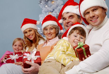 Portrait of happy family in Santa caps with affectionate boy holding giftbox with his father near by photo