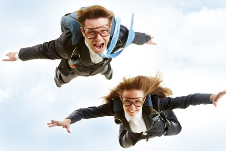Conceptual image of young business partners flying with parachutes on their backs photo