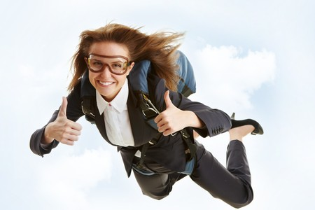 woman flying: Conceptual image of young female flying with parachute and showing thumbs up Stock Photo