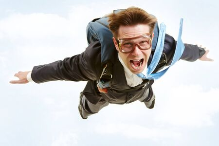 Conceptual image of young businessman flying with parachute on back Stock Photo - 7873844