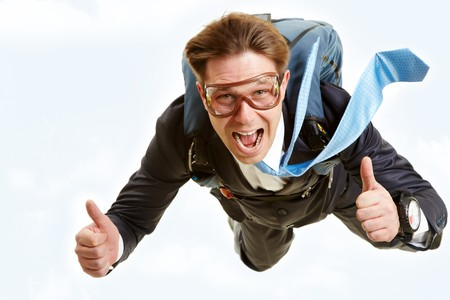 Conceptual image of happy man flying with parachute and showing thumbs up photo