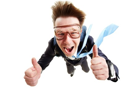 flying man: Conceptual image of happy man flying with parachute and showing thumbs up