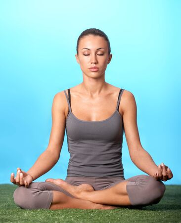 Portrait of young woman meditating in pose of lotus in isolation photo
