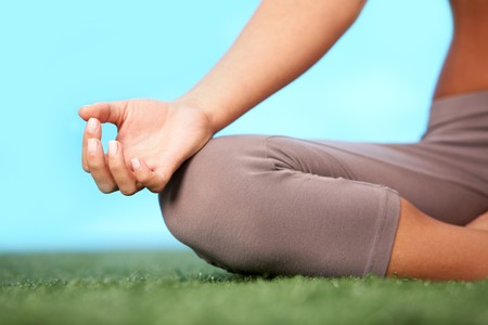 Close-up of female�s knee during meditation in pose of lotus with her legs crossed photo