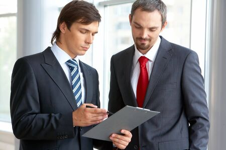 Image of confident businessman looking at document in partner�s hand while discussing it photo