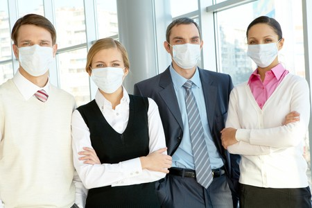 Portrait of business team in protective masks looking at camera photo