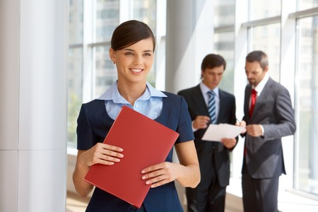 Portrait of confident female looking aside with working colleagues at background photo