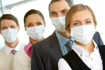 Pretty female in protective mask looking at camera on background of business people photo