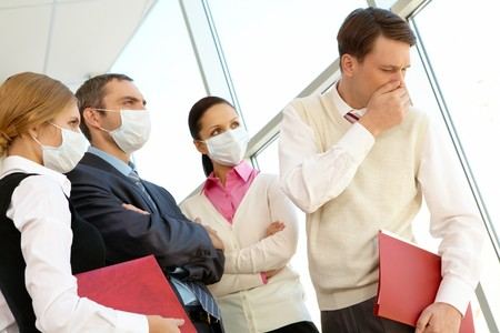 strictly: Group of associates in protective masks looking strictly at coughing man Stock Photo