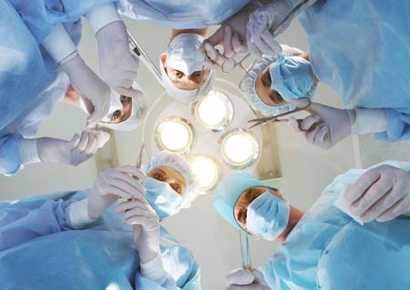 quirurgico: Vista desde abajo de cirujanos experimentados con herramientas m�dicas durante la operaci�n