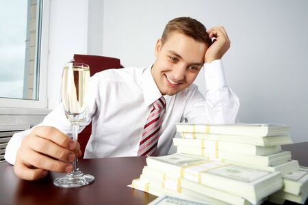 Image of young successful employer looking at heap of dollar bills and touching glass with champagne on workplace Stock Photo - 7873884