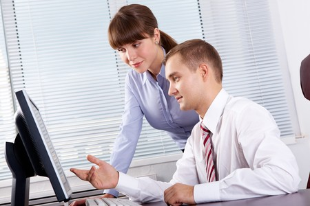 Successful businessman explaining something to his pretty colleague while they looking at monitor photo