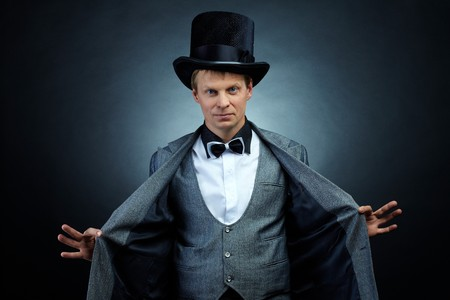 Image of male magician in hat and tail-coat looking at camera photo
