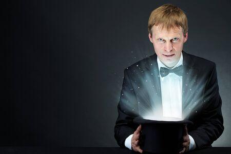 Imagen de mago masculino celebración de sombrero con luz mágica y mirando la cámara  Foto de archivo