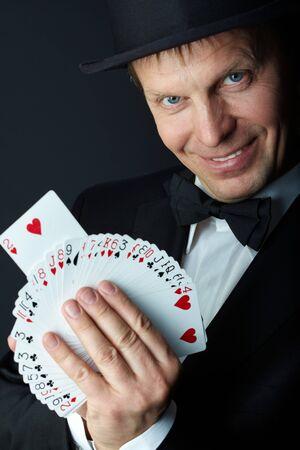 truc: Foto van mannelijke goochelaar met kaarten kijken camera op zwarte achtergrond