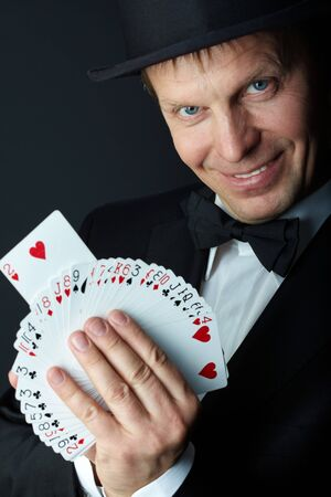 Image of male magician with cards looking at camera on black background photo