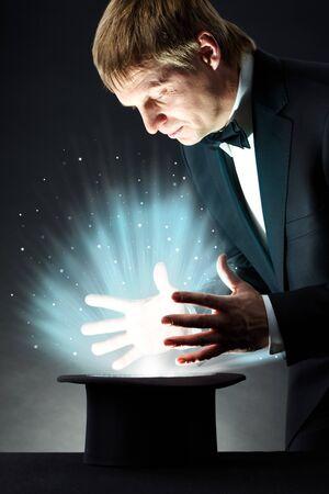 sombrero de mago: Imagen de mago masculino estudiando sombrero con la magia de luz en la oscuridad  Foto de archivo