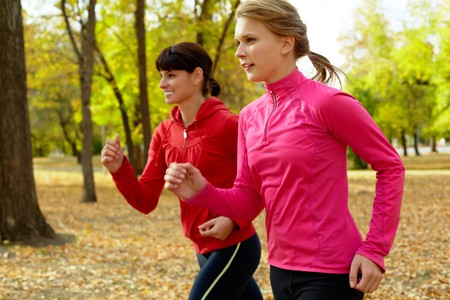 girl in sportswear: Two young women jogging in autumn park Stock Photo