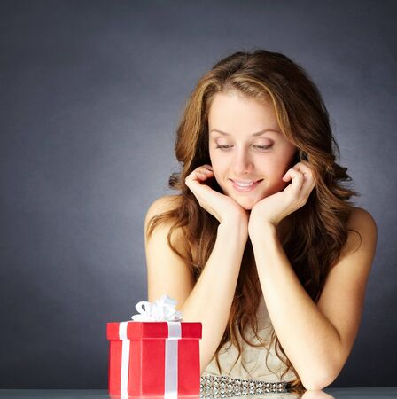 amused: Portrait of a girl sitting and looking at a gift box
