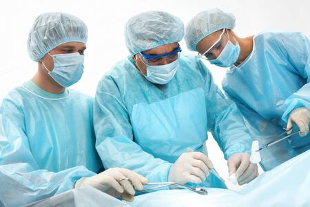 Three surgeons operating on a patient Stock Photo - 7964910