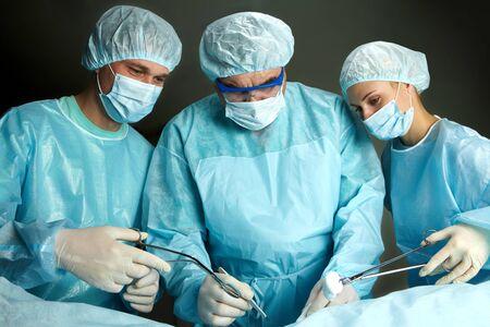 Three surgeons working against dark background Stock Photo - 7964951