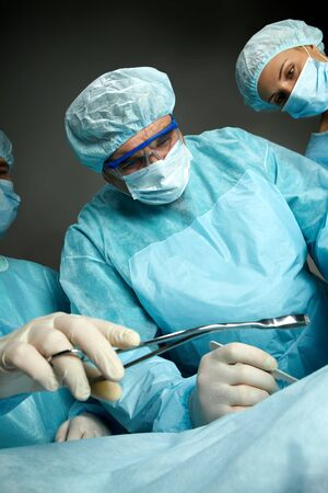 Side view of three surgeons operating Stock Photo - 7964926