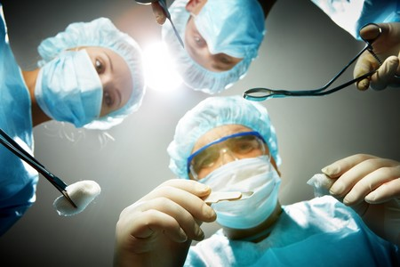 Three surgeons bending over a patient Stock Photo - 7964886
