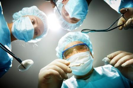 cirujano: Tres cirujanos agacharse un paciente