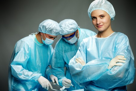 A young female surgeon against her two male colleagues  Stock Photo - 7964934