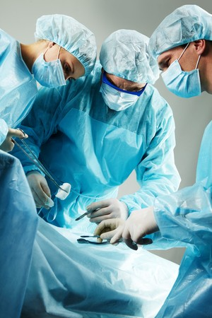 Three surgeons busy with a patient Stock Photo - 7964948