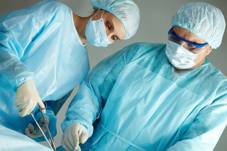 A surgeon and a nurse operating Stock Photo - 7964943