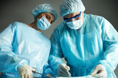 Senior doctor operating and a nurse standing with a clamp   Stock Photo - 7964949