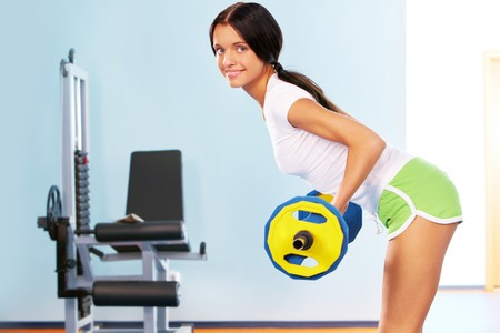 active girl lifting dumbbell - building muscle photo